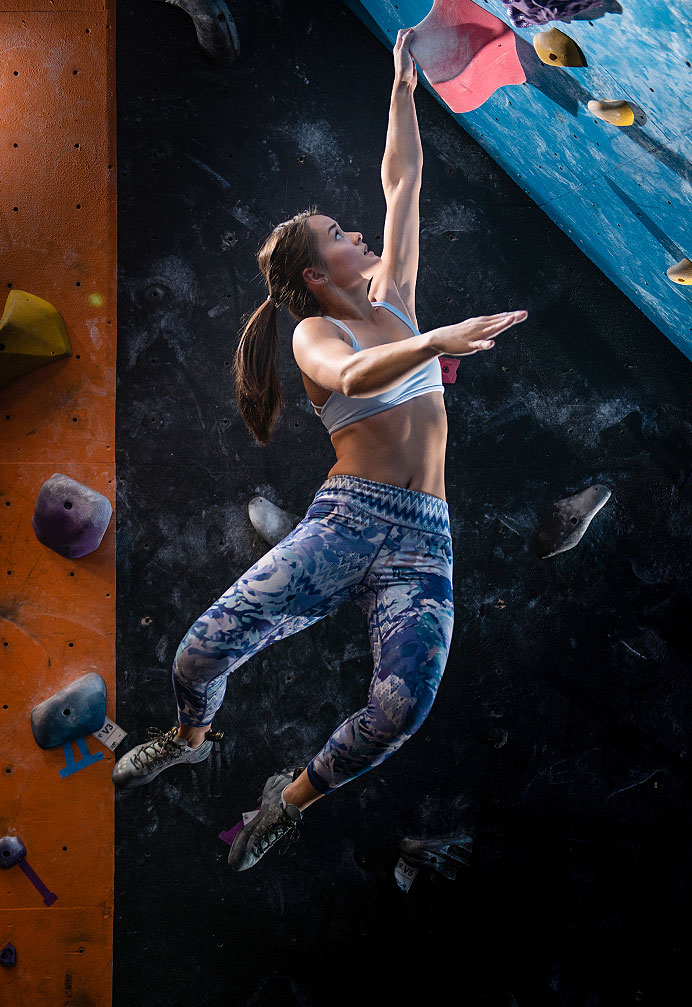 Female bouldering climber hanging
